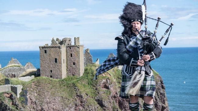 Gaitero con traje típico escocés en el Castillo de Dunnottar