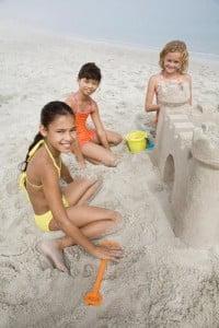 gente en la playa niños y su castillo de arena