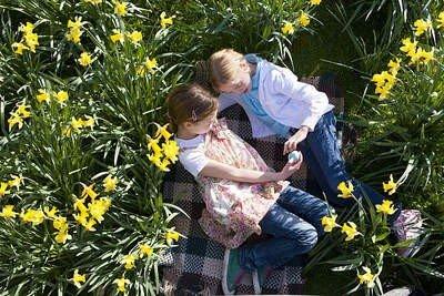 Niñas en un hermoso parque con flores.