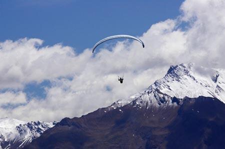 Paraglider sobre las montañas  del parque Aspiring, Nueva Zelanda, Aventura